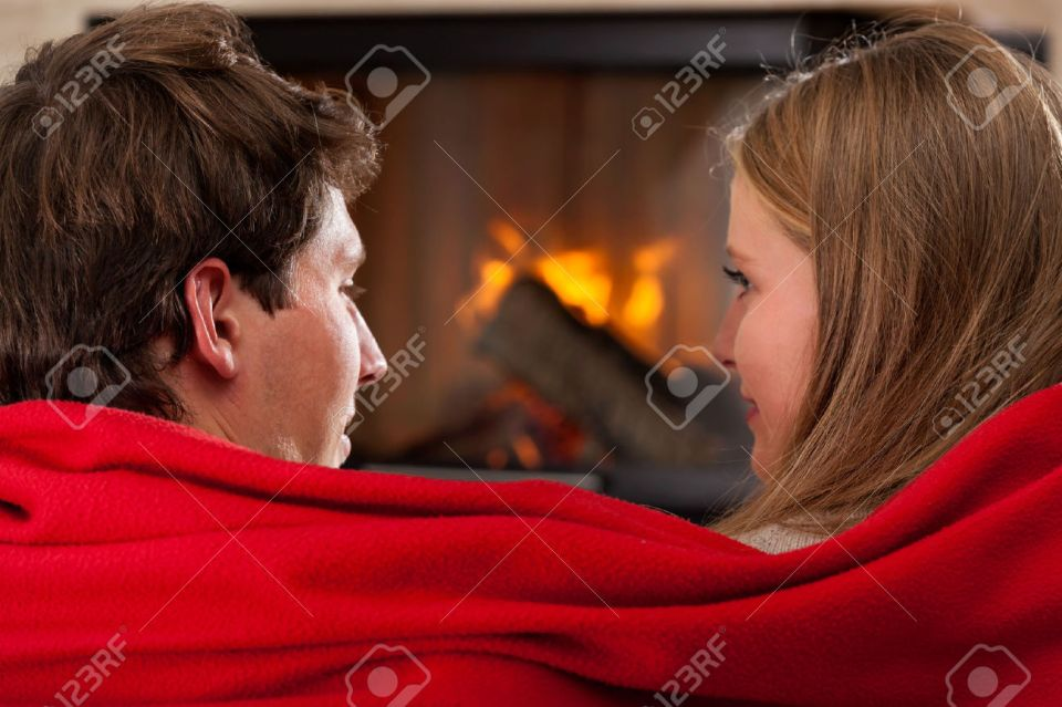 24568564-A-couple-cuddling-under-a-cosy-red-blanket-Stock-Photo-couple